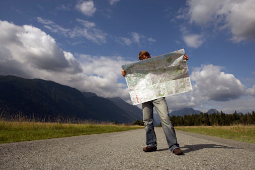 Image of man standing on rural road reading road map