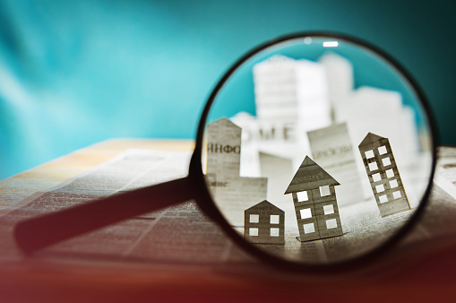 Image of paper house under a magnifying lens