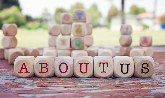 About us word written on cube shape wooden blocks on wooden table